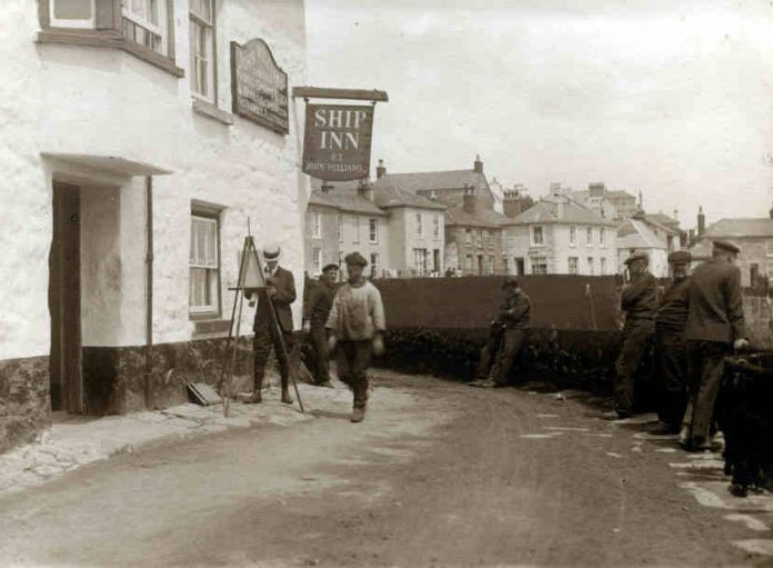 T.H. Victor at work painting outside the Ship Inn in Mousehole (Courtesy of Newlyn Archive)